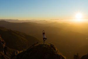 A holistic personal trainer doing yoga outside