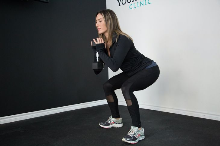 Woman doing squats as part of a weight loss circuit workout.