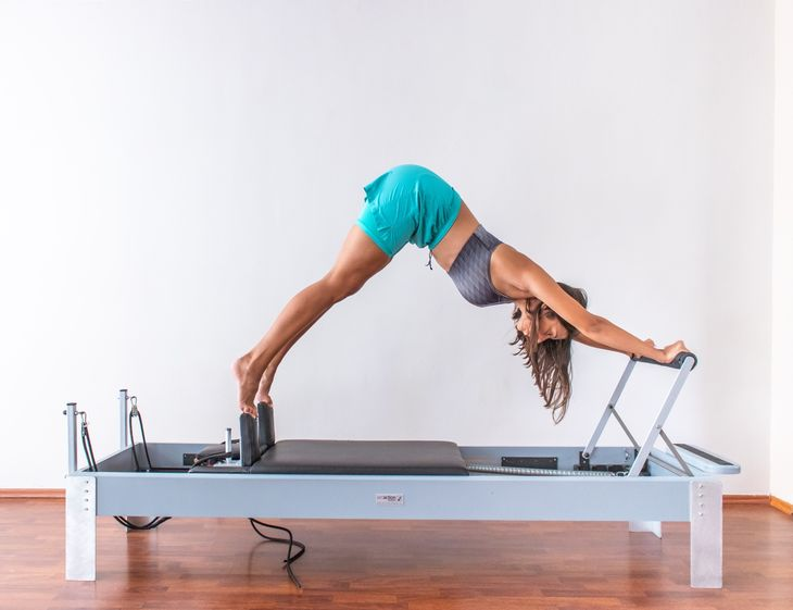 Pilates personal trainer on a reformer