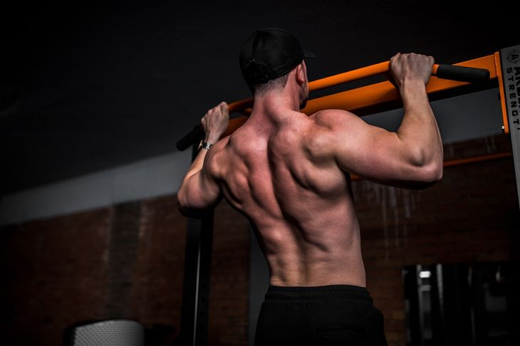 A man in a dark gym completing calisthenics exercises for beginners
