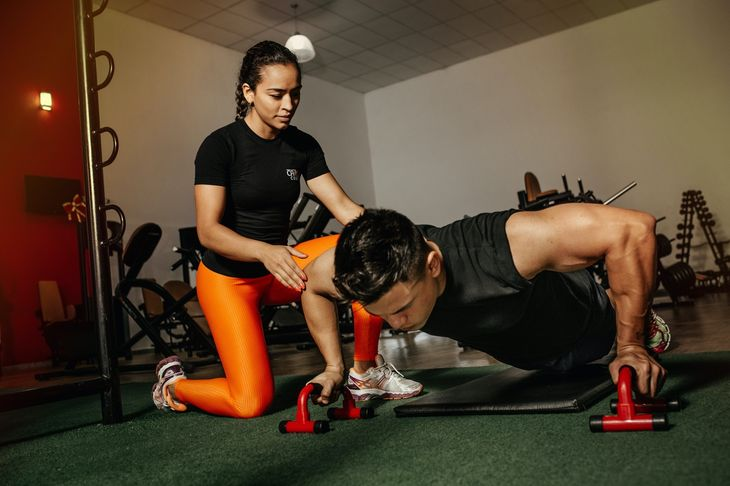 Personal trainer working with a client in a gym