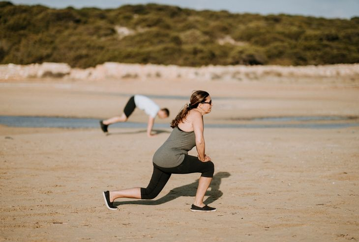 Personal trainer doing lunges as part of a total body HIIT workout.