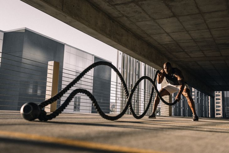 A weight loss personal trainer with battle ropes