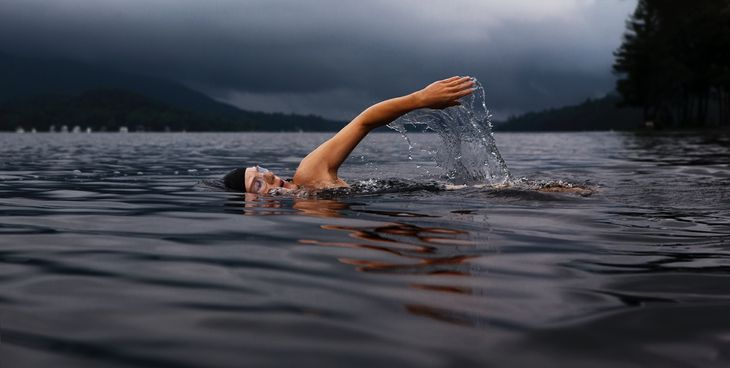 Personal trainer swimming in a lake